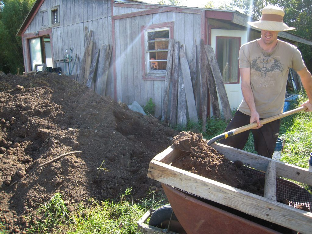 Shoveling compost onto a flat screen. Photo by Wren Vile
